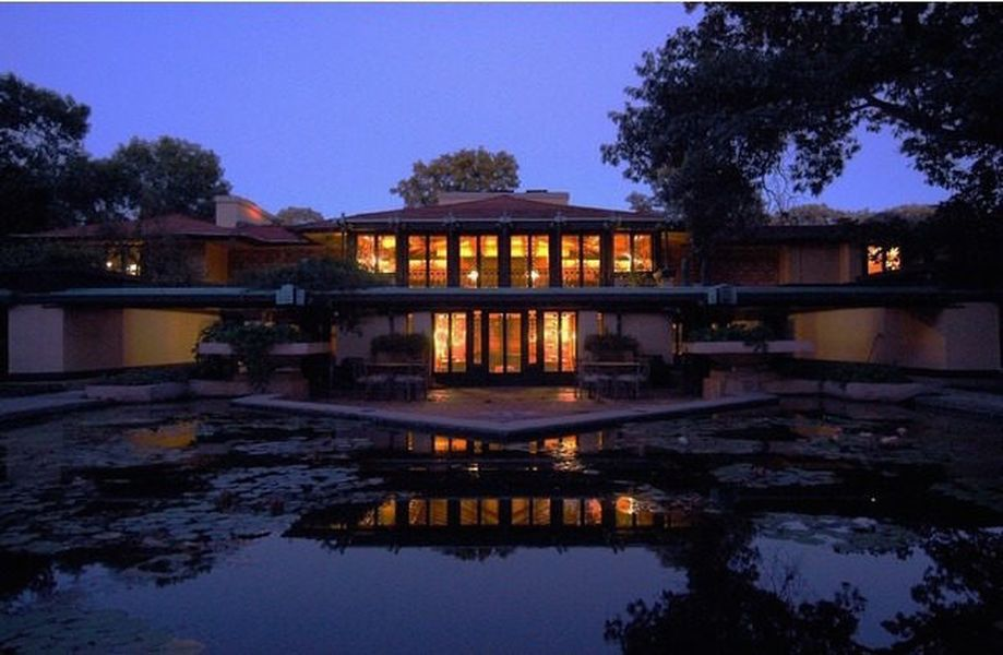 The Avery Coonley House by Frank Lloyd Wright. The house has many tall windows. It is evening and the lights within the house are illuminated against a dark blue evening sky. There is a body of water in the foreground.