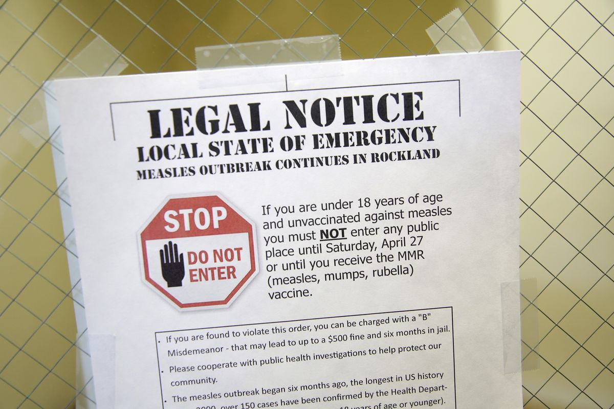 FILE - This Wednesday, March 27, 2019 file photo shows a sign explaining the local state of emergency because of a measles outbreak at the Rockland County Health Department in Pomona, N.Y. Measles is spread through the air when an infected person coughs o