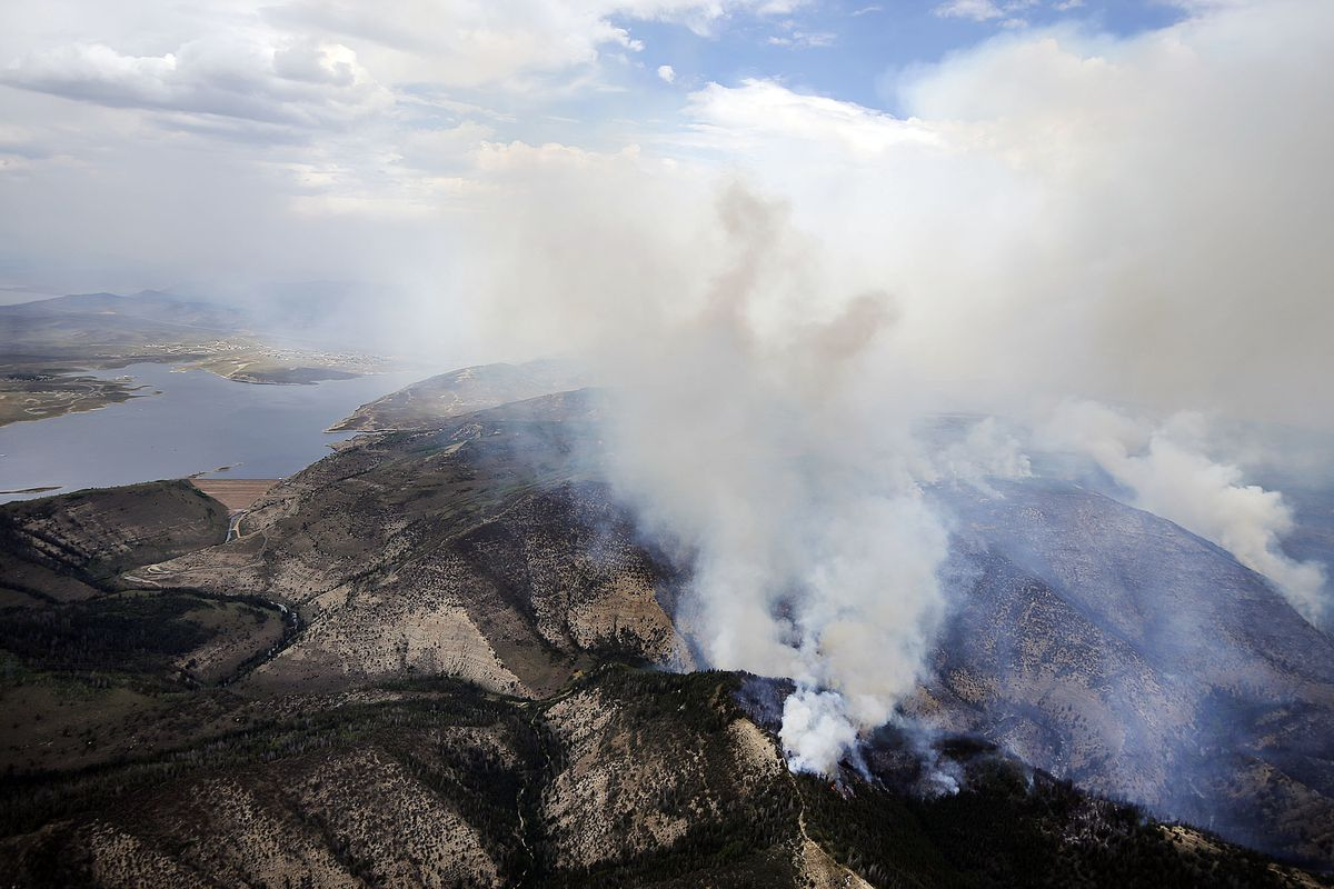 FILE- In this July 5, 2018, file photo, smoke rises from a wildfire near Strawberry Reservoir in Utah. This year is projected to be among Utah's worst in terms of land burned. Estimates show more than $47 million have been spent on Utah's wildfires so far