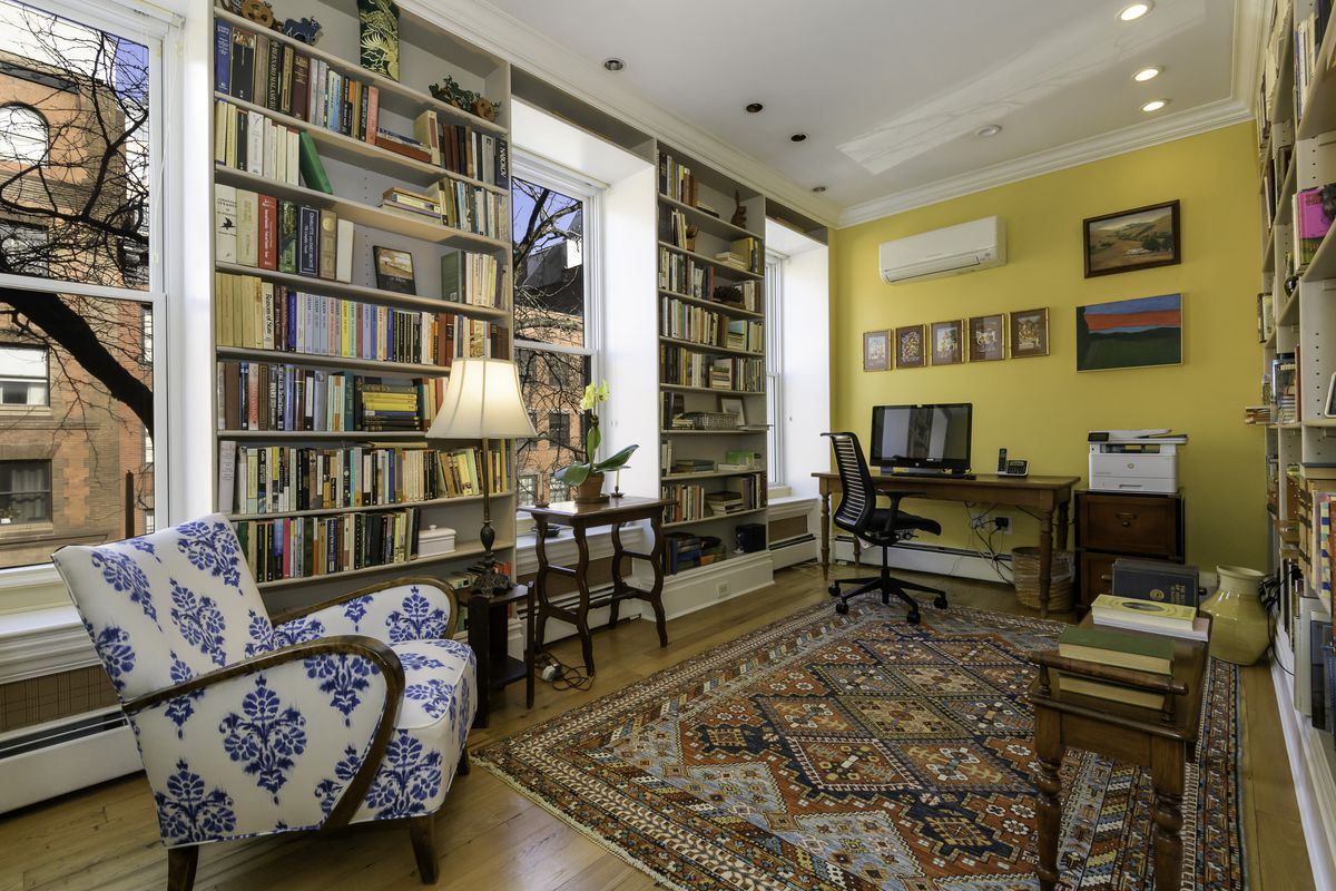 A bright yellow room with two walls of floor-to-ceiling built-in shelving.