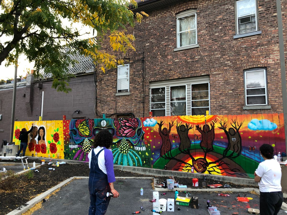 """Josémanuel Hernandez is seen here working on the mural """"Earth People."""" To the right is Hernandez's friend Cauria Duarte, who helped paint it."""