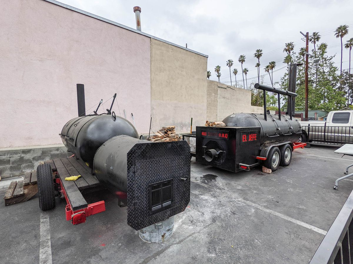 Two long black offset barbecue smokers in a parking lot on an overcast day.