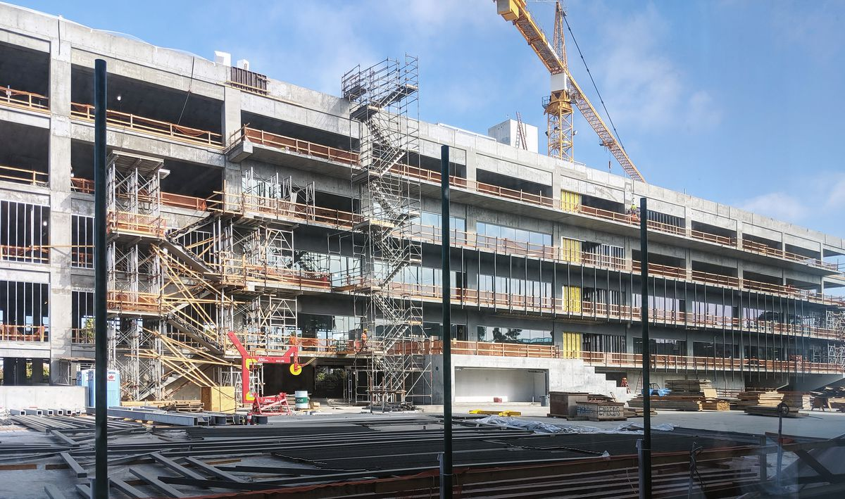 A construction photo showing scaffolding, a crane, and an under-construction building.