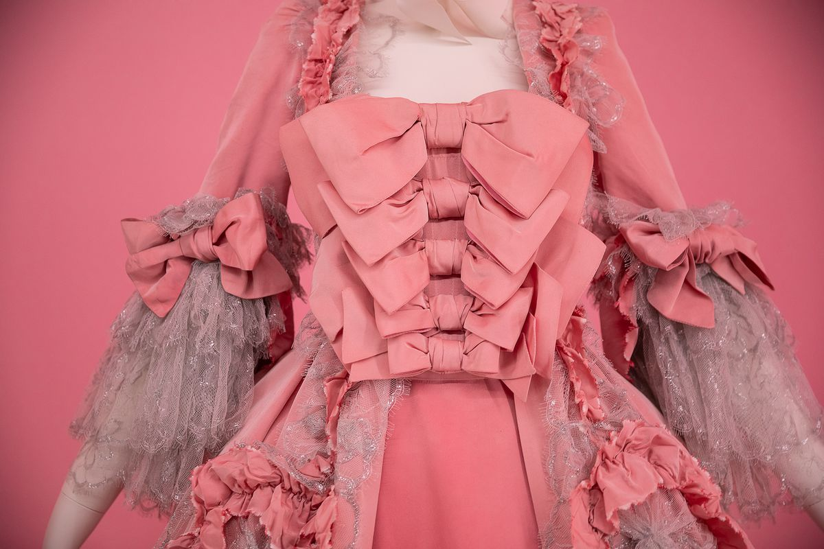 A ruffled dress with numerous pink bows running down the front.