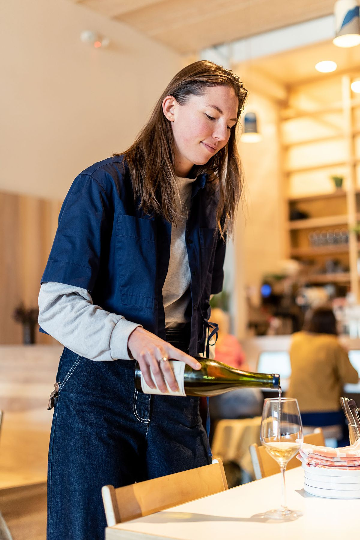 Kae Whalen pours wine for a table of customers at Kismet.