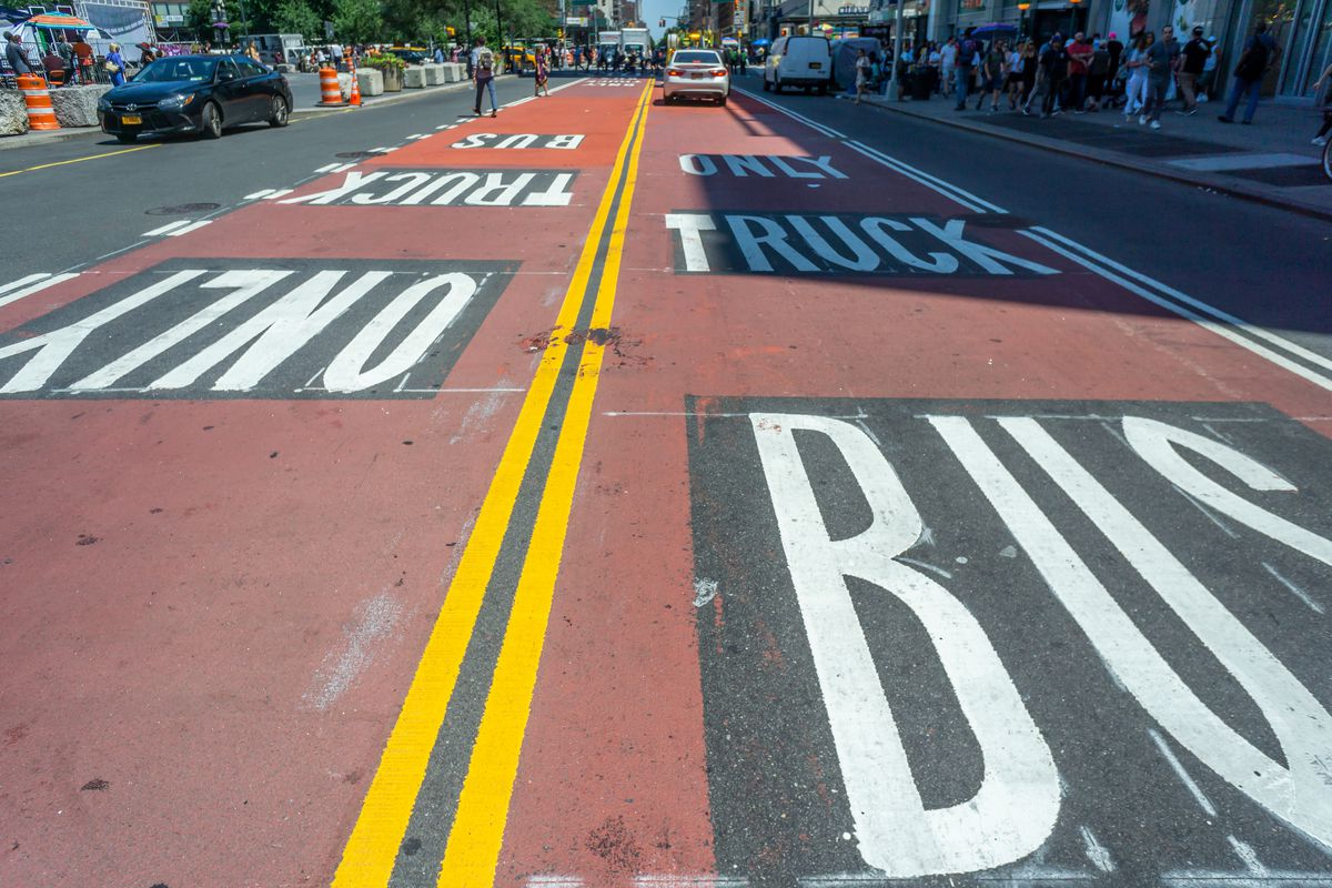 """A maroon painted busway on 14th Street with """"Truck Bus Only"""" in white print over it. A double yellow line separates the two lanes in the street."""