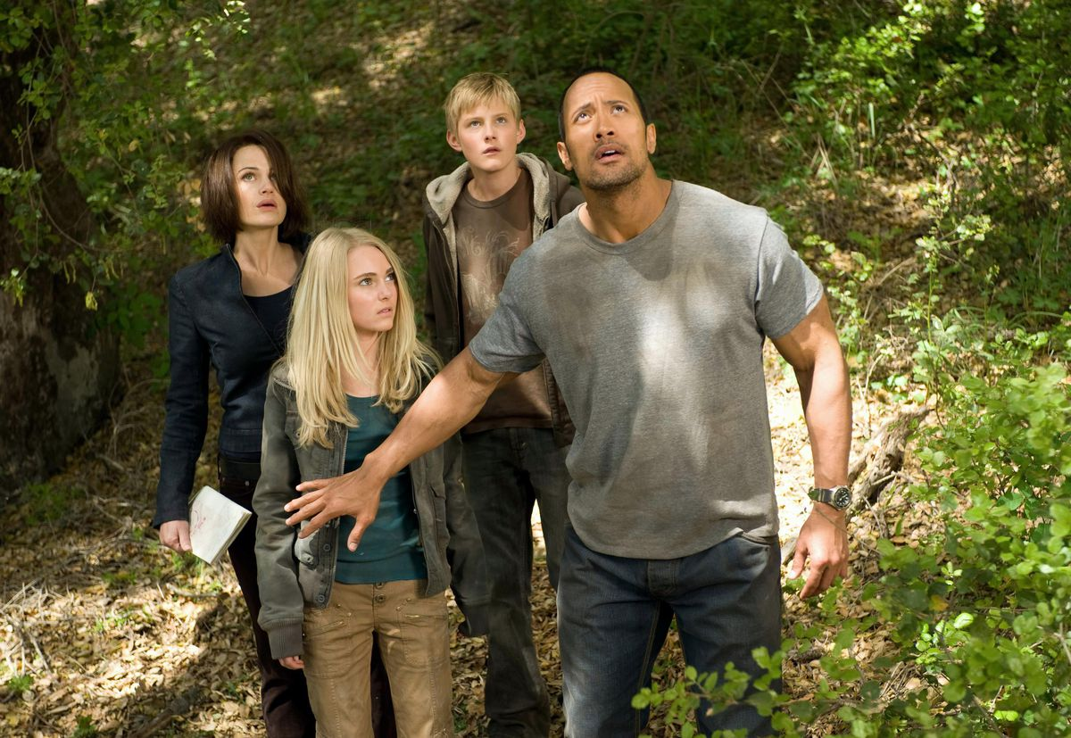 the rock holds back two alien kids and a mom as they look into the sky