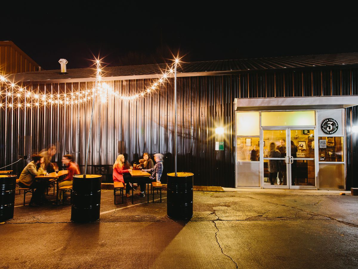 An outdoor dining area outside of a brewery. The brewery has a dark metal exterior. There are string lights hanging over the dining area. There are patrons drinking at tables.