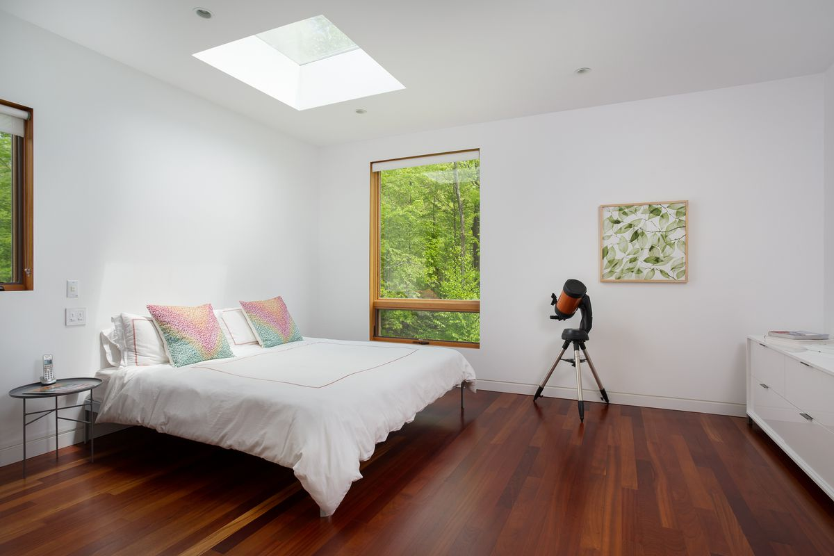 A white bed sits on wood floors with white walls. There's a telescope standing nearby.