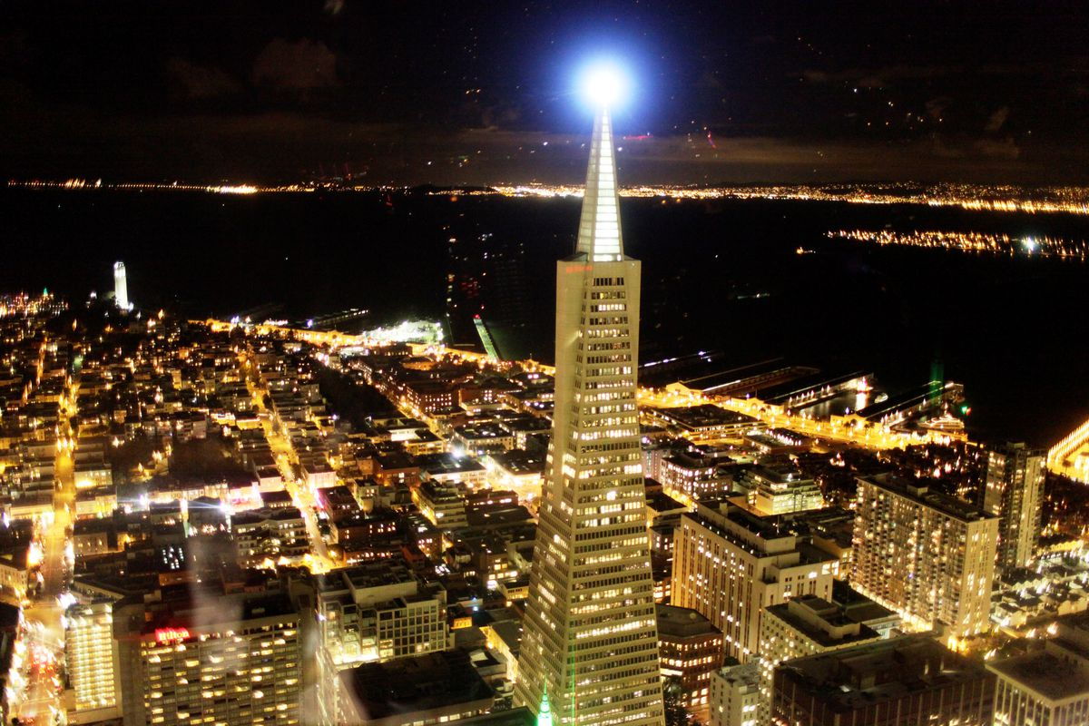 A photograph of San Francisco at night with the beacon lit on top of the Transamerica Pyramid.