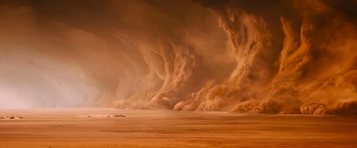 a giant sand storm approaches a car chase in the middle of a desert