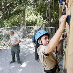 Logan Flanagan, 11, climbs a rock wall during activity time at Camp Tracy in Mill Creek Canyon on Friday, July 22, 2016.