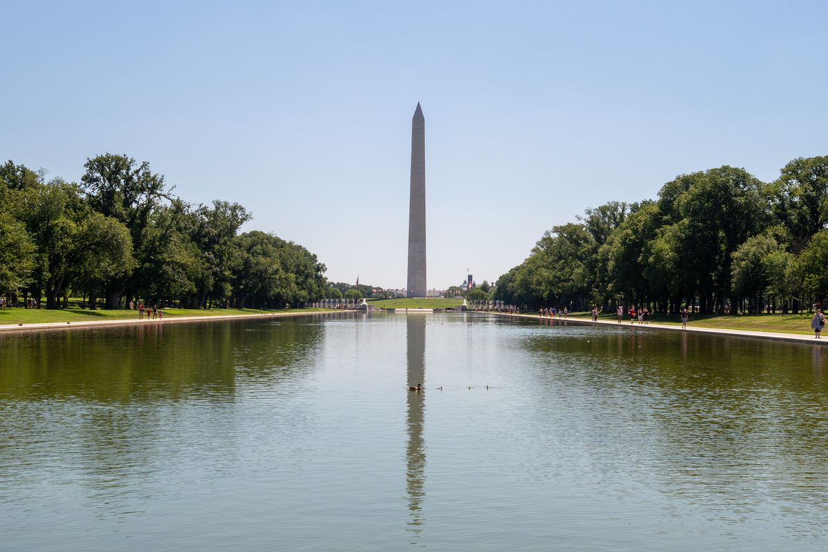 A long and wide reflecting pool with a large obelisk in the background. There are trees along the pool's promenade.