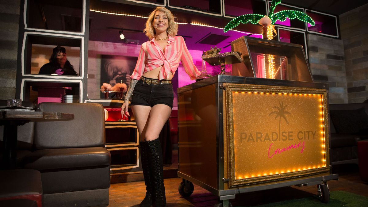 A woman stands next to an ice cream cart