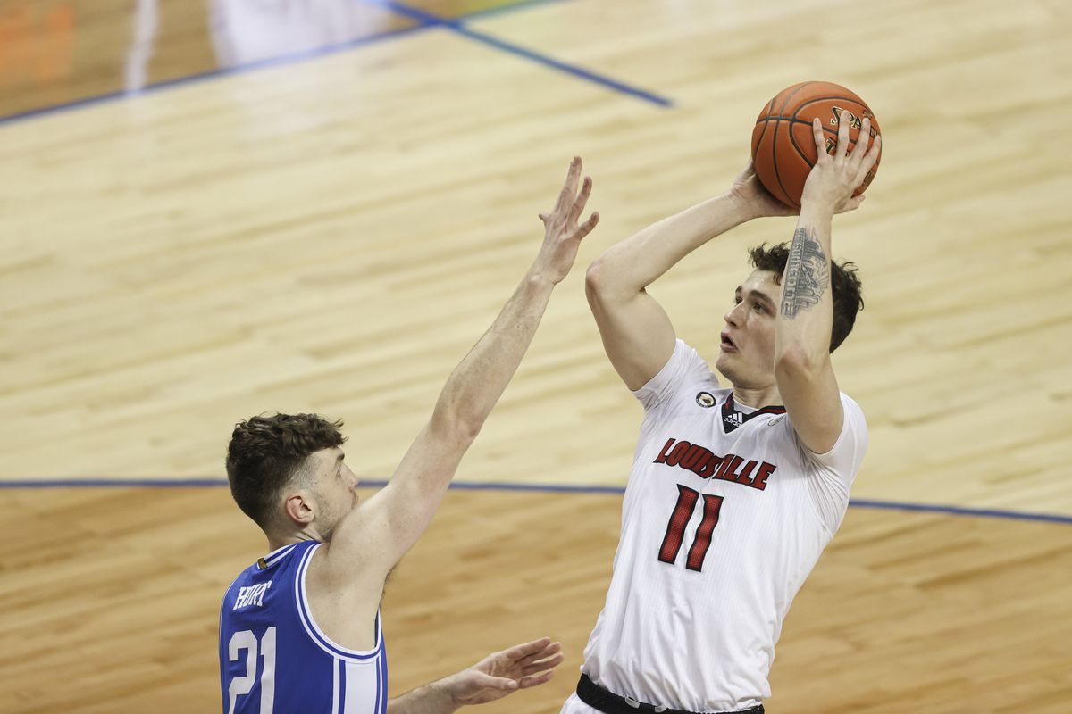 Louisville Cardinals forward Quinn Slazinski shoots against Duke Blue Devils forward Matthew Hurt during the first half in the second round of the 2021 ACC tournament at Greensboro Coliseum.