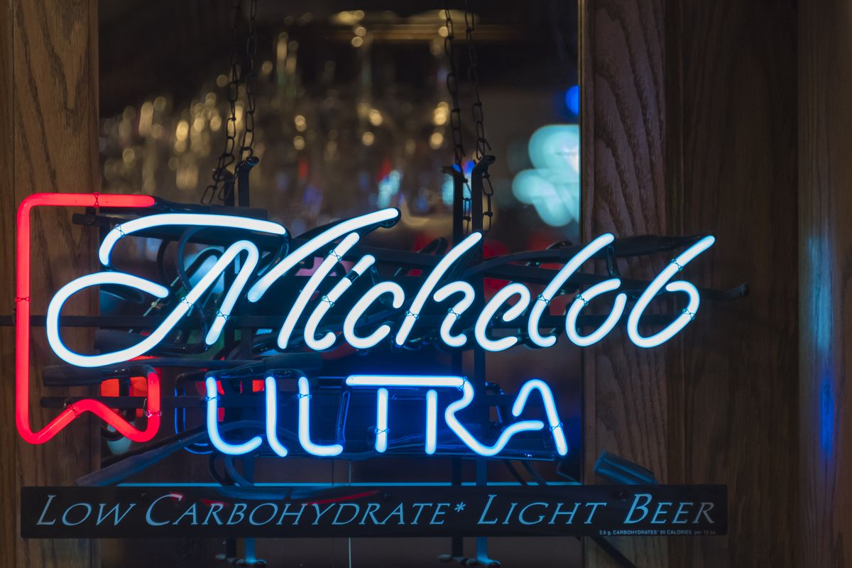 Michelob Ultra beer written in neon glow light inside a bar in New York City, USA.