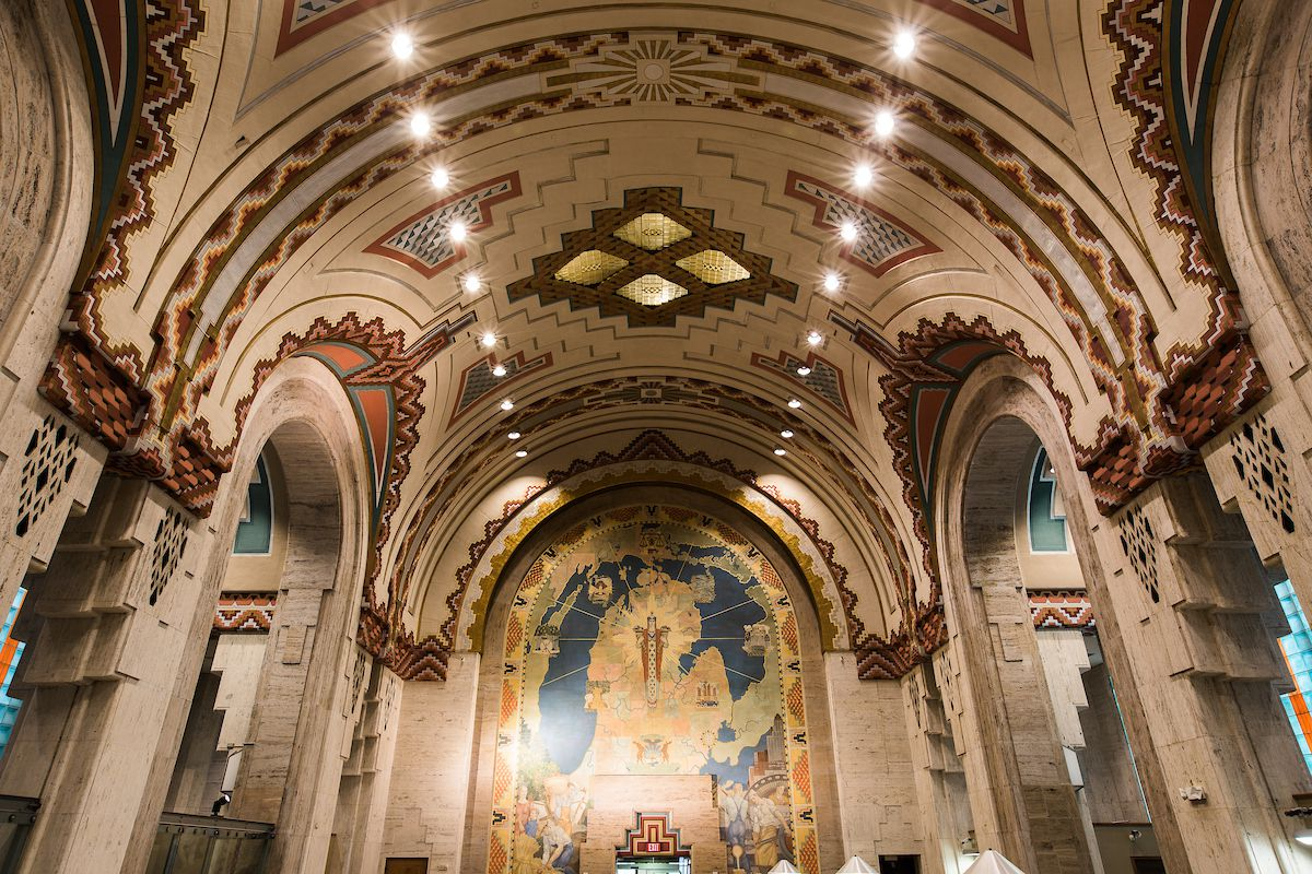 The interior of the Guardian Building in Detroit. The ceiling and walls have an inlaid design. The ceiling is curved and there are columns. There is a mural on one wall.