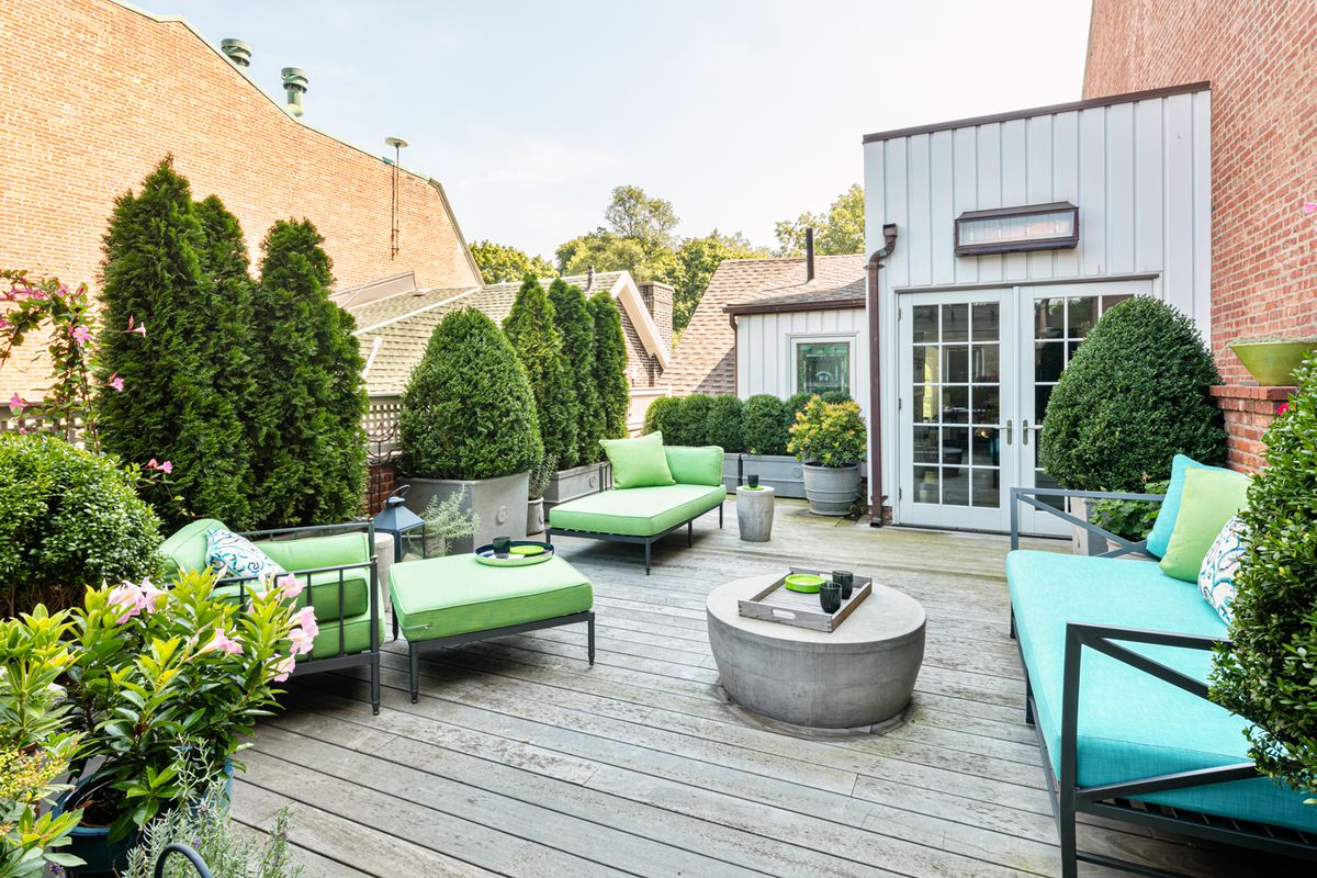 A roof deck with several green and blue chairs and multiple plantings.