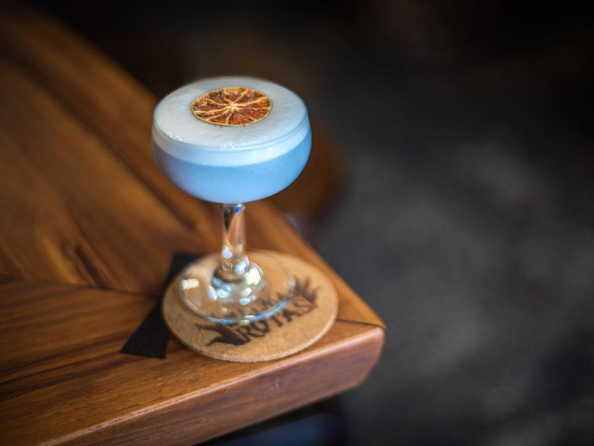 blue cocktail in long-stemmed coupe on wood table