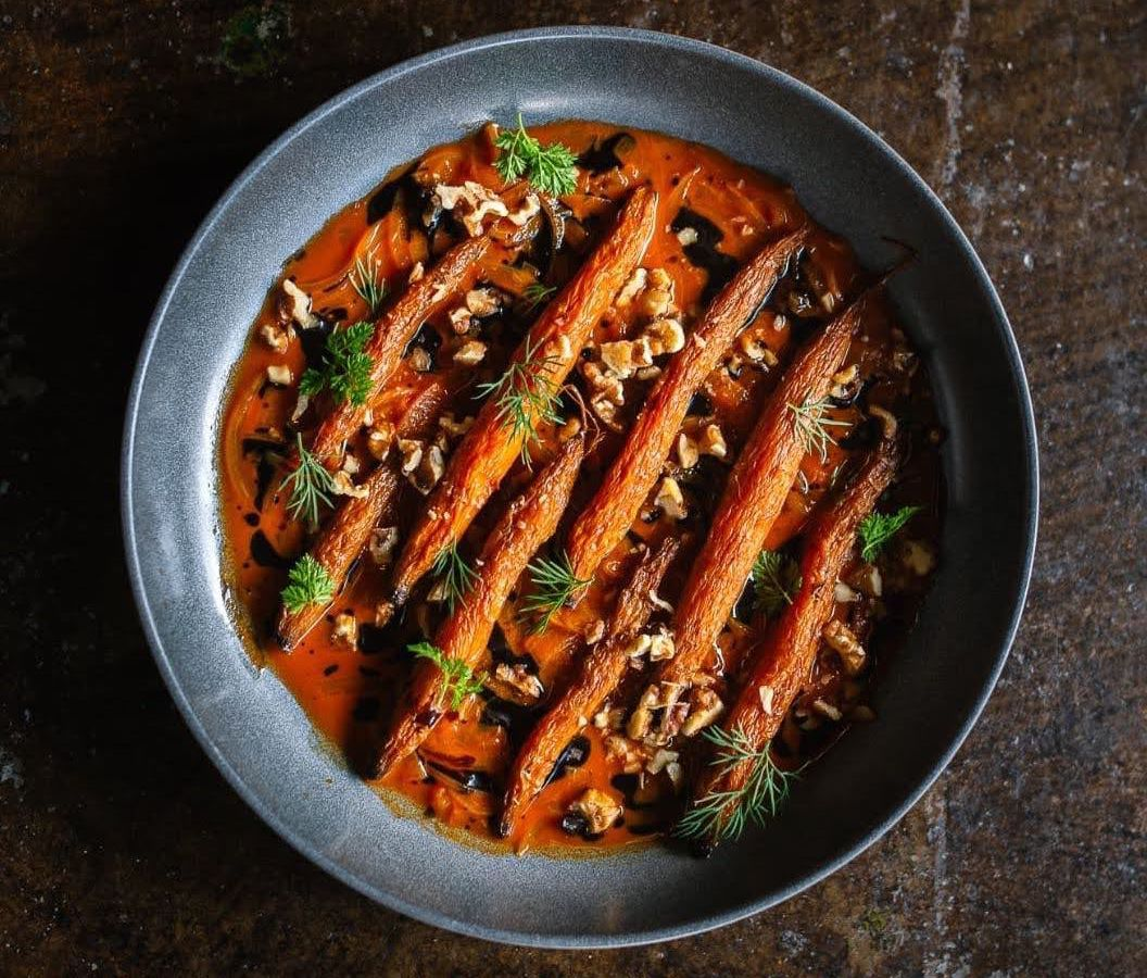 A slate-looking plate with long carrots in sauce topped with herbs and nuts on a textured stone background