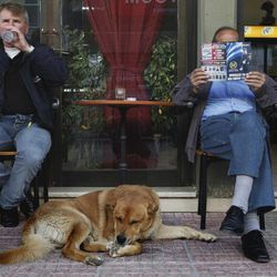 In this Thursday, April 26, 2012 photo a man, right, reads a Golden Dawn party election pamphlet given to him by a party member, at a coffee shop in the suburban town of Artemis, 25 kilometers (15 miles) east of Athens, on Thursday, April 26, 2012. Reeling from a vicious financial crisis that has cost them pensions and jobs, Greeks have been turning away in droves from the mainstream politicians they feel have let them down.Firmly on the fringe of the right since it first appeared 20 years ago, Golden Dawn garnered a meager 0.23 percent in the 2009 elections. But its popularity has shot up over the past few months and support stood at about 5 percent in recent opinion polls, well above the 3 percent threshold needed to enter parliament.
