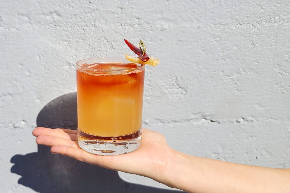 A white hand holds out, flat-palmed, a cocktail in a glass that glows orange and red, with a spicy garnish.