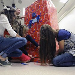 Air Force Tech Sgt. Edward Goettig along with his wife, Tracie, and two daughters Sydney, left, and Bailee wrap up a box as Edward would be the surprise for his youngest daughter Olivia, whose 10th birthday it was at Fox Hollow Elementary School in Lehi on Thursday, March 6, 2014. Goettig had been deployed to Afghanistan since Aug. 27, 2013.