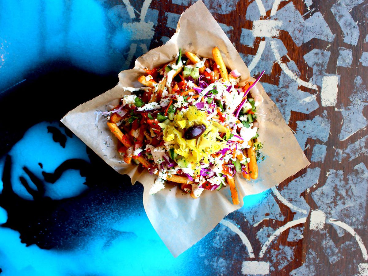 As seen from above, a tray of fries with gyro meat, slaw, and peppers on top.