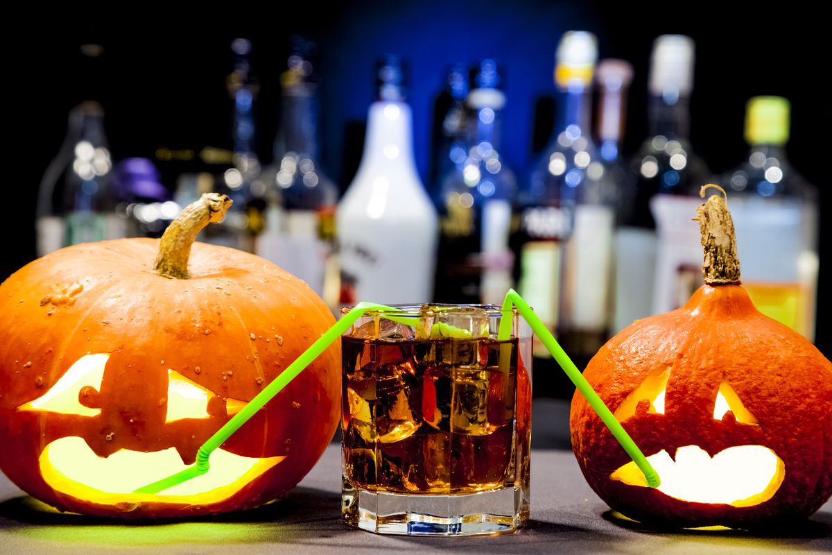 two carved pumpkins with straws in a glass of whiskey