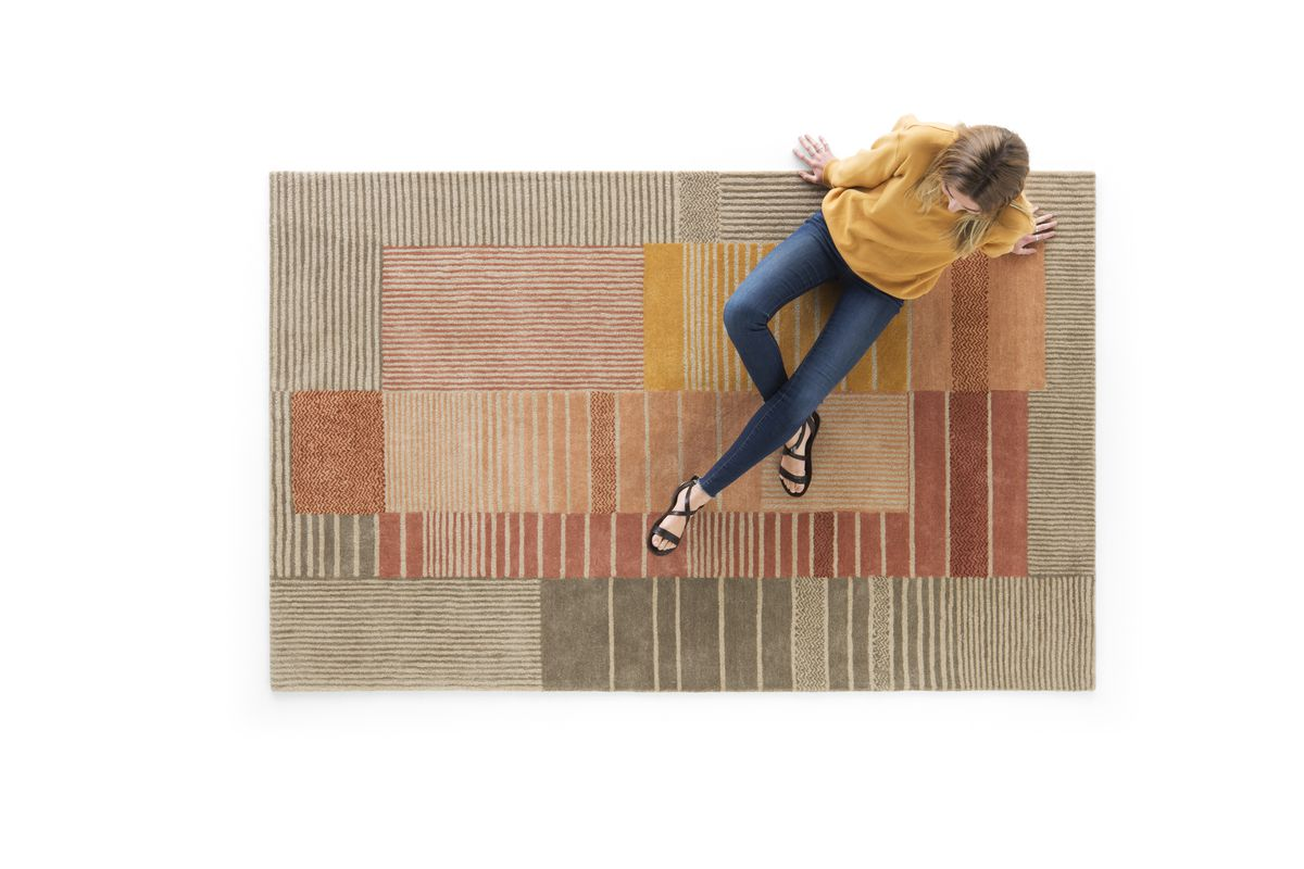 Woman sitting on red, orange, and yellow rug.