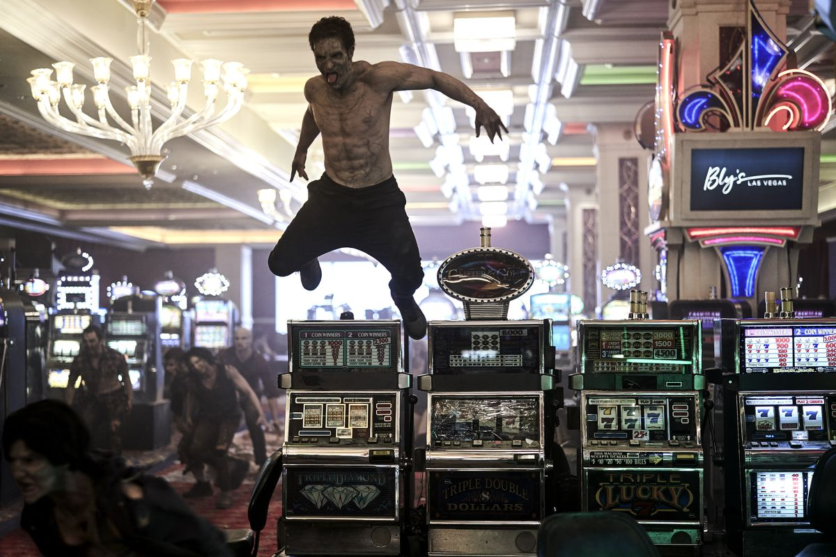 A shirtless zombie leaps through the air over a bank of slot machines as a horde of undead invade a casino in Army of the Dead