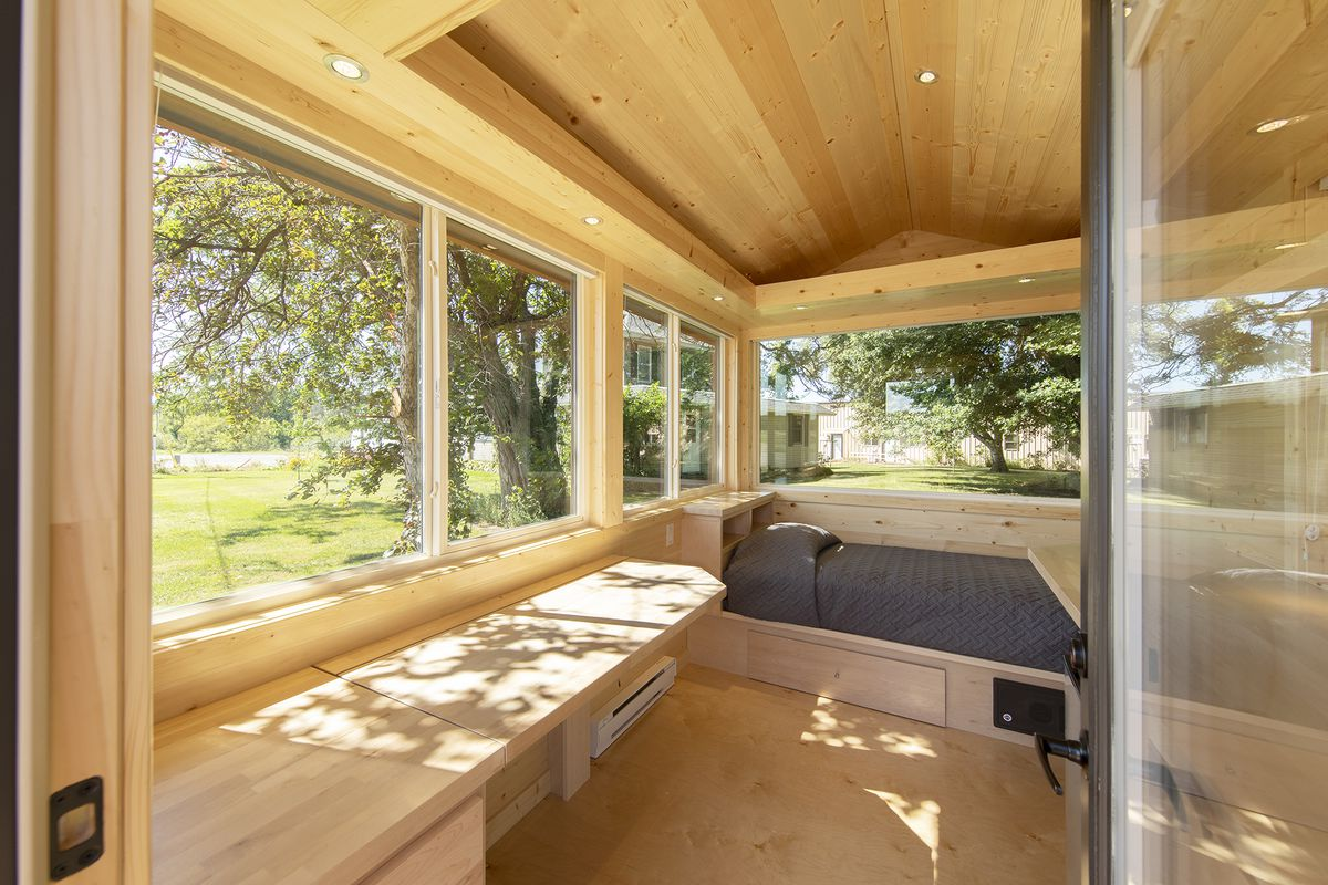 Inside of a pitched roof small dwelling with large windows on all sides. There is a built-in bed and bench.