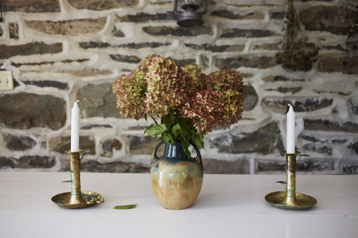 Two skinny white candles are positioned on each side of a vase of flowers in front of a stone wall.