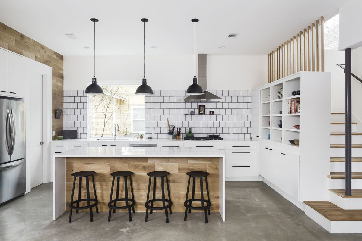 The kitchen has white cabinets and a white and warm wood island, with black stools, black light fixtures and stainless steel appliances.