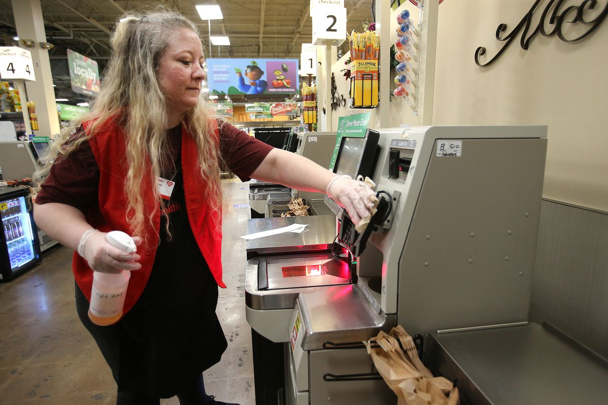 Cashier Steph Manson cleans the self checkout stations after each transaction at Smith's Marketplace in West Jordan on Tuesday, March 31, 2020.