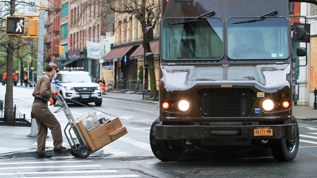 A UPS worker pushing a cart of boxes is seen wearing a mask as he makes his deliveries on an empty NYC street.