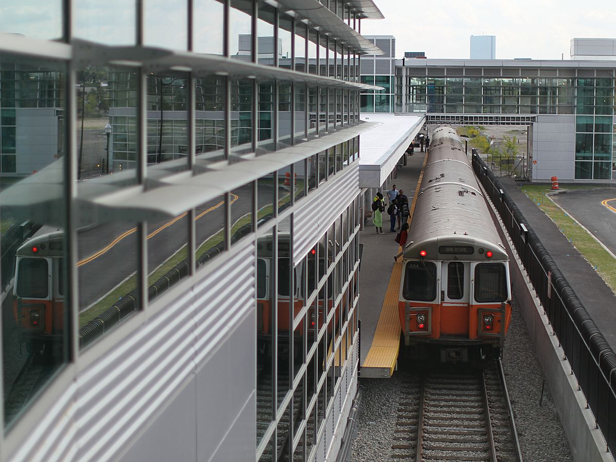 A subway train leaving a station as viewed from the top of the train.
