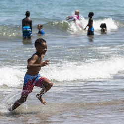 Kids enrolled in the Chicago Park District summer camp at Nichols Park play in Lake Michigan at 57th Street Beach near Promontory Point on the South Side, Wednesday afternoon, July 24, 2019.