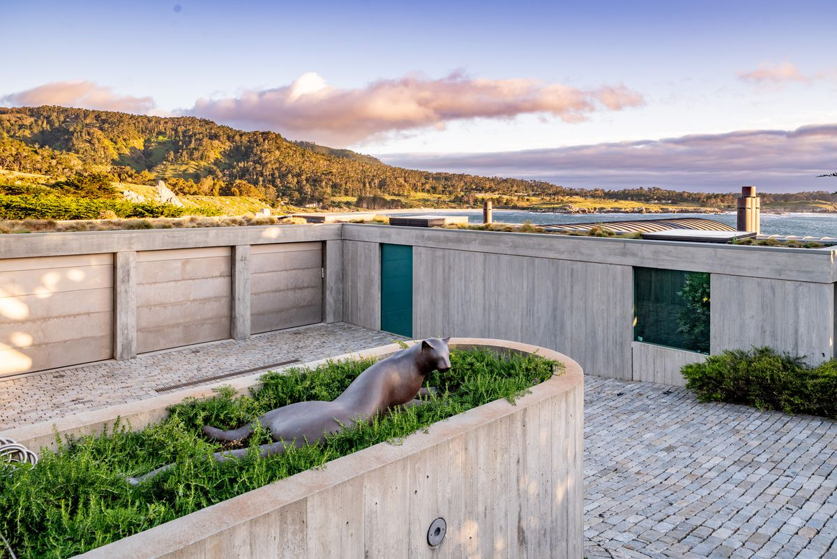 An exterior view of a bunker-looking home that is built into the landscape from concrete. A bronze leopard statue sits in a green planter.