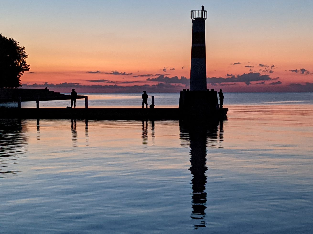 Anglers, trying for early Chinook, on the east jetty at the mouth of Montrose Harbor silhouetted in the pre-dawn half light. Credit: Dale Bowman