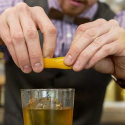 To get the citrus oils in the drink, he squeezes the oil from an orange peel over the drink.