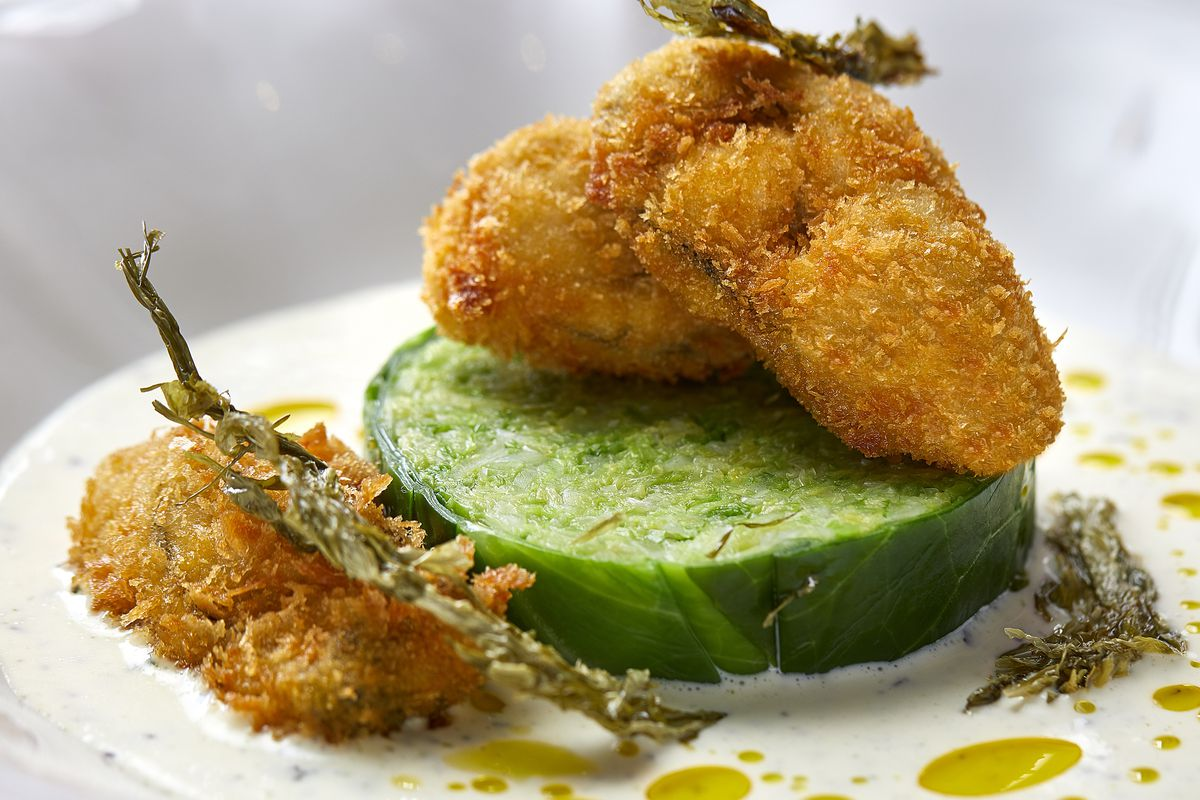 Deep-fried, breaded oysters on a white plate at Siren