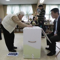 A South Korean elderly woman casts her vote for the parliamentary election at a polling station in Seoul, South Korea, Wednesday, April 11, 2012.