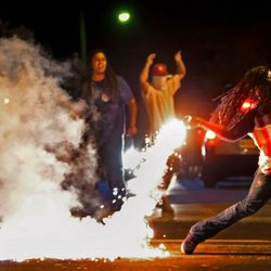 FILE – In this Aug. 13, 2014, file photo Edward Crawford Jr., returns a tear gas canister fired by police who were trying to disperse protesters in Ferguson, Mo. Six young men with connections to the Ferguson protests, including Crawford, have died, drawing attention on social media and speculation in the activist community that something sinister is at play. Police say there is no evidence the deaths have anything to do with the protests and note that only two were homicides. But activists and observers remain puzzled and wonder if they'll ever get answers. Crawford fatally shot himself in May 2017 after telling acquaintances he had been distraught over personal issues, police said. (Robert Cohen/St. Louis Post-Dispatch via AP, File)