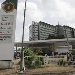 A man leans against a price board at a Nigerian National Petroleum Corporation petrol station in Lagos, Nigeria, Tuesday, April 24, 2012. For the price of cheap gasoline, Nigeria paid billions of dollars into a corrupt government system of fuel subsidies that saw huge contracts awarded to shady companies without any oversight, according to a lawmakers' report.