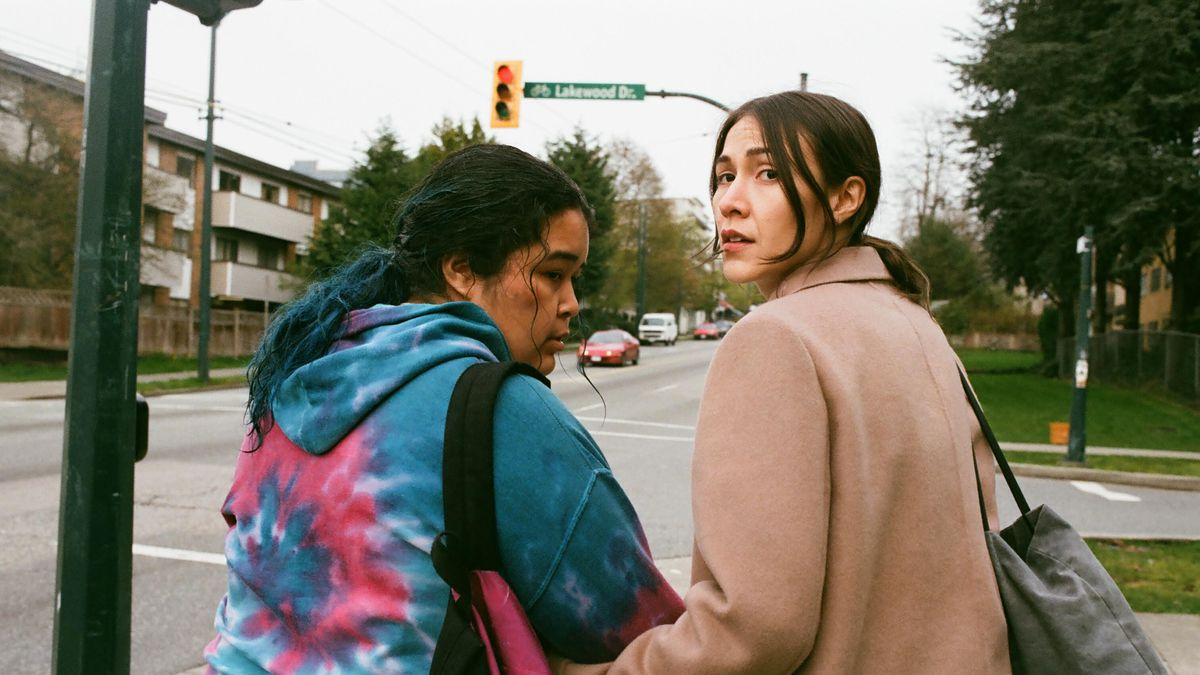 Two women, walking arm in arm, take a look behind them.