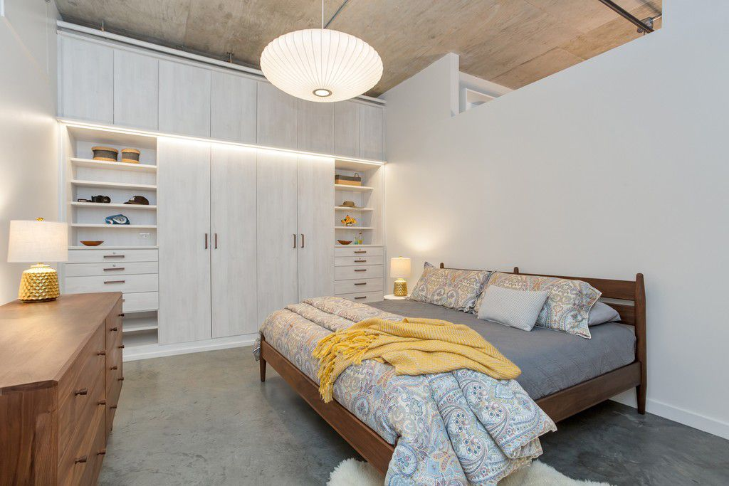A white bedroom with a gray bed and carpet.