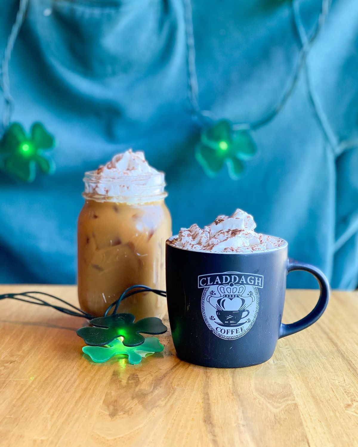 Iced latte in a jar and hot latte in a black branded Claddagh Coffee mug. Both are topped with whipped cream and dusted cocoa powder.