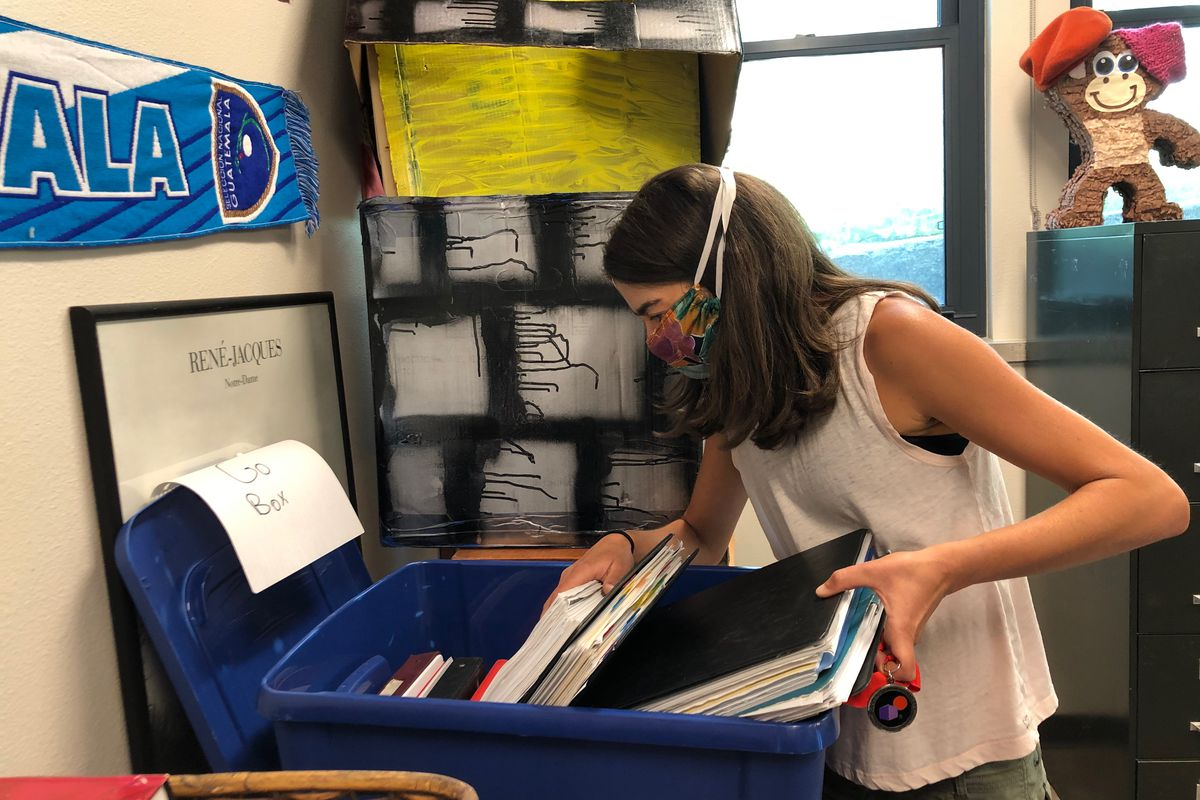 Masked teacher prepares supplies in case she has to leave the classroom quickly.