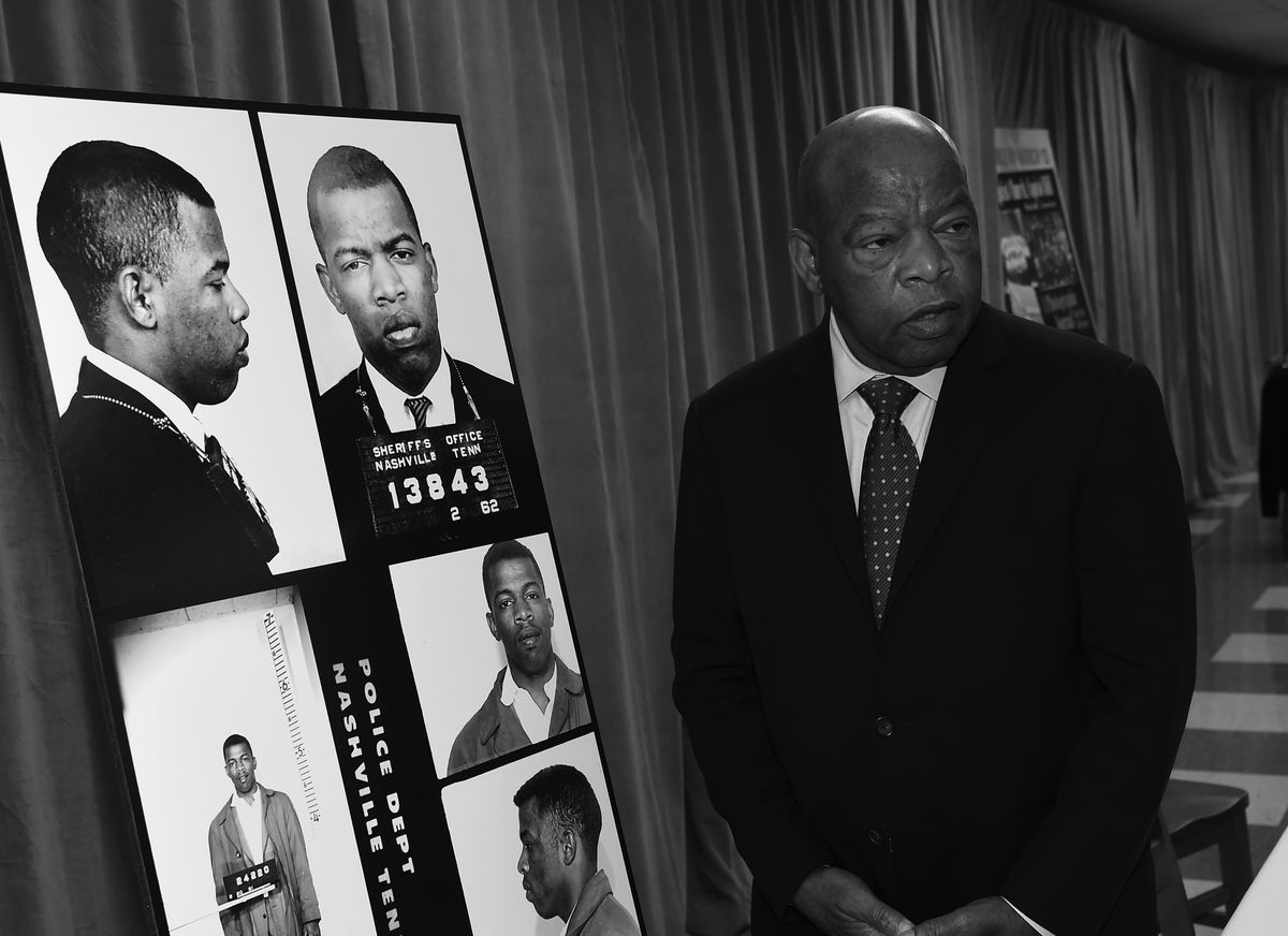 In a black and white photo, Lewis, in a dark suit, looks at five images of his younger self — all mugshots — taken following various arrests.